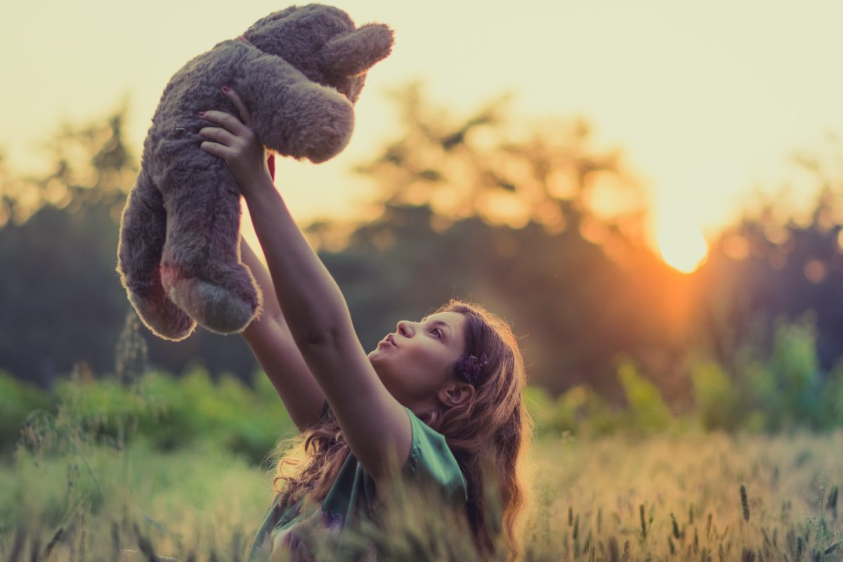 Girl holding teddy bear up to they sky at sunset